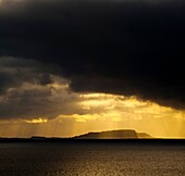 Scotland, Western Isles, Isle of Soay Dramatic shafts of light from the settin sun above the Isle of Soay, viewed from Elgol on the Isle of Skye