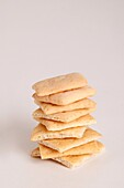 Close-up of organic wheat crackers stacked high on top of each other on a white background