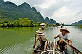 China guangxi yangshuo a chinese couple rowing on a bamboo raft on the yulong river with tourists on board