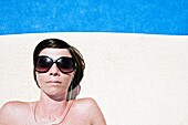 Shot of an Attractive Brown Haired Woman Next to the Pool with her Earphones