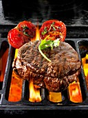 Beef fillet steaks & tomatoes being cooked on a bbq.