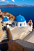 Oia, Ia Santorini - Blue domed Byzantine Orthodax churches, - Greek Cyclades islands .