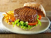 Beef burger in a wholemeal bun with salad and french fries