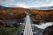 Wooden swing bridge across a river in a rocky landscape with birch trees north of the arctic circle, Saltdal, Junkerdalen national park, trekking tour in Autumn, Fjell, Lonsdal, near to Mo i Rana, Nordland, Norway, Scandinavia, Europe