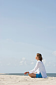 Woman practicing yoga at sandy beach, List, Sylt, Schleswig-Holstein, Germany