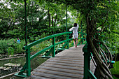 Woman on the Japanese Bridge and the White Water Lily Pond in the Impressionist Painter Claude Monet's Water Garden, Giverny, Eure (27), France