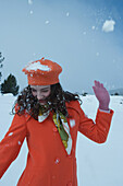 Teenage girl being hit with snowball, looking away, smiling