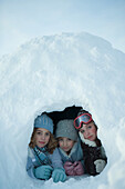 Three young friends lying in igloo, smiling at camera