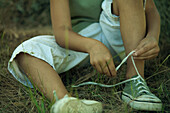 Little boy sitting on the ground, tying shoelaces, cropped view