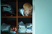 Baby boy peeking out of shelf, looking away
