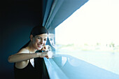 Woman pressing fists against window, smiling at camera