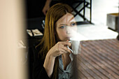 Young woman drinking coffee in cafe, looking out window