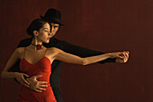 Couple tango dancing together, holding hands, arms outstretched, man looking at camera