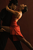 Couple tango dancing together, man holding woman's leg, woman leaning back