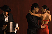 Couple dancing together next to male accordion player