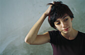 Young woman scratching head, looking away, blurred