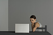 Woman sitting at table, watching laptop computer, hand under chin
