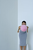 Woman bending over, holding balloon in mouth, looking at camera