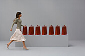 Woman walking past row of shopping bags, side view