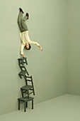 Man balancing on one hand on tall stack of chairs