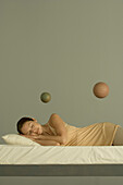 Woman sleeping in bed, two spheres floating in the air above her