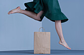 Female jumping over shopping bag, low section