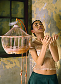 Woman standing beside empty birdcage with hands raised, feathers floating around her