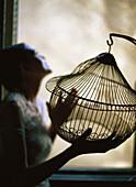 Woman standing beside window, holding empty birdcage