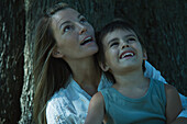 Mother sitting beneath tree with son in lap, both looking up