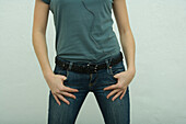 Female wearing jeans, hands in pockets, mid section