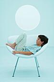 Boy reclining on chair, eyes closed