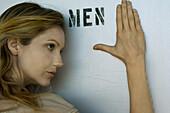 Woman resting head and hand against men's room door