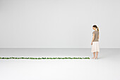 Woman standing, smiling down at vine growing on floor