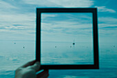 Person holding picture frame in front of seascape
