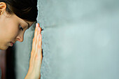 Woman leaning head against wall looking down