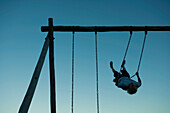 Young man swinging on swing set, backlit