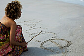 'Woman crouching on beach, writing word ''peace'' in sand with stick'