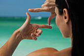 Woman at beach, looking at sea through finger frame