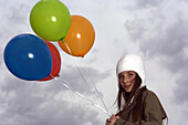 Female with balloons out on cloudy day