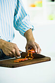 Slicing fresh red bell pepper on cutting board