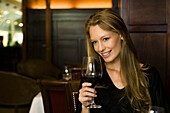Woman enjoying glass of red wine in restaurant