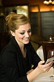 Woman text messaging in restaurant