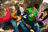 Young friends chatting together, one holding acoustic guitar
