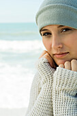 Teenage girl at the beach, dressed in warm clothing, portrait