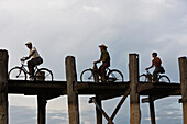 Amarapura, Myanmar, people cycling across U Bein Bridge
