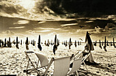 Closed parasols and beach chairs on beach, b&w, toned