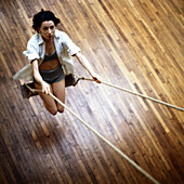 Young woman on swing, indoors, high angle view