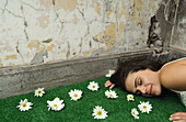 Woman lying on artificial turf scattered with flowers, surrounded by flaking walls