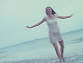 Female in dress standing on beach with arms out, full length