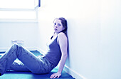 Young woman sitting on floor, leaning against wall
